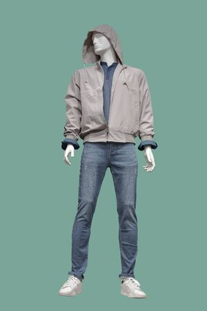 Full length male mannequin dressed in jacket with hood and blue jeans, isolated on green background. No brand names or copyright objects.