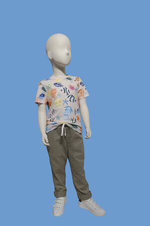 Full length child mannequin dressed in casual clothes, isolated on blue background. No brand names or copyright objects.
