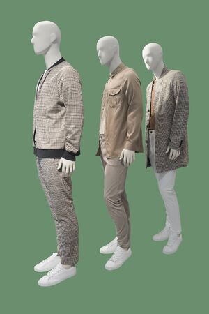 Three male mannequins dressed in casual clothes, isolated on green background. No brand names or copyright objects.