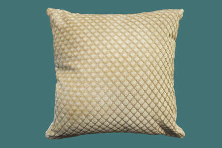 Beige decorative pillow. Isolated on green background. 스톡 콘텐츠