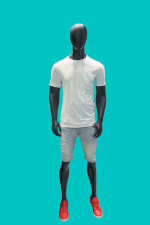 Full length male mannequin dressed in white t-shirt and jeans shorts, isolated on green background. No brand names or copyright objects.