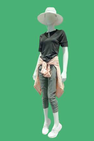 Full length female mannequin dressed in summer casual clothes, isolated on green background. No brand names or copyright objects.