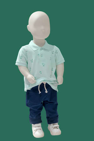 Full length child mannequin dressed in fashionable kids wear, isolated on green background. No brand names or copyright objects.