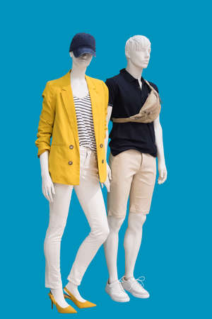 Full length two mannequins, male and female, dressed in fashionable clothes, isolated on a blue background. No brand names or copyright objects.