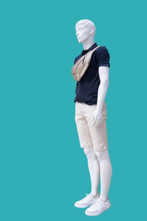 Full length male mannequin dressed in fashionable summer clothes, isolated on a green background. No brand names or copyright objects.