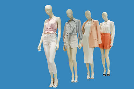 Four female mannequins dressed in fashionable clothes isolated on a blue background. No brand names or copyright objects. 免版税图像 - 157956529