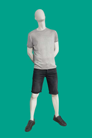 Full length male mannequin dressed in knitted t-shirt, isolated on green background. No brand names or copyright objects.