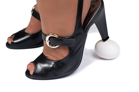 Womans high heels stepping on a egg