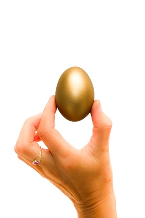 Womans hand holding a golden egg
