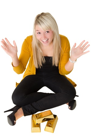 goldbars: Young happy girl with goldbars sitting on the floor with hands in the air. Over white background Stock Photo