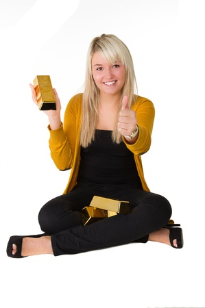 goldbars: Young happy girl with goldbars sitting on the floor giving thumbs up Over white background