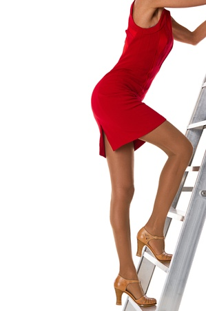 latter: Woman in red dress climbs to the top of the latter of succes Stock Photo