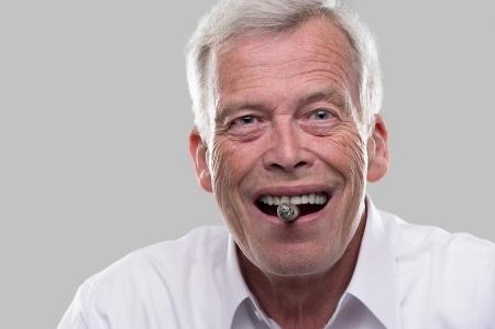 Gelukkige oude man met een sigaar in zijn mond en een grote glimlach.