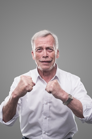 handsome old man: Smiling senior holding his fists up and are ready