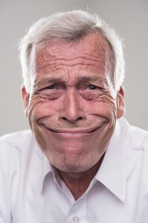 Humoristisch portret van een gepensioneerde grijze haren senior man met een brede stralende glimlach, dat het idioom belichaamt, grijnzend van oor tot oor