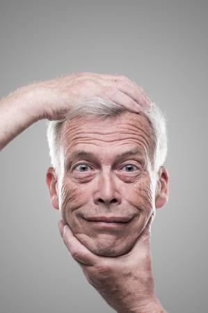 Humoristisch macabere zelf portret van een senior man die zijn eigen lachende gezicht op een armlengte afstand voor een inspectie op een grijze achtergrond studio Stockfoto