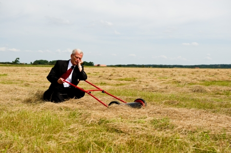 An exhausted businessman rest on his knees with his lawnmower in a field of harvested grain as he prepares to reap the rewards of all his hard labour and perseverance, conceptual image Stock Photo