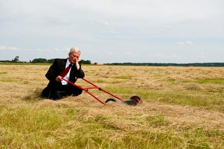 Een uitgeputte zakenman rusten op zijn knieën met zijn grasmaaier in een veld van de geoogste graan als hij zich voorbereidt om de vruchten van zijn harde werk en doorzettingsvermogen plukken, conceptueel beeld Stockfoto