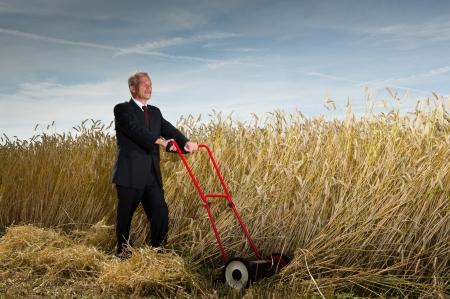 Seniot executive zakenman pauzeren tijdens de uitdaging van de oogst een gebied van rijpe tarwe met een hand grasmaaier als hij visualiseert de beloningen te winnen bij de voltooiing van zijn taak