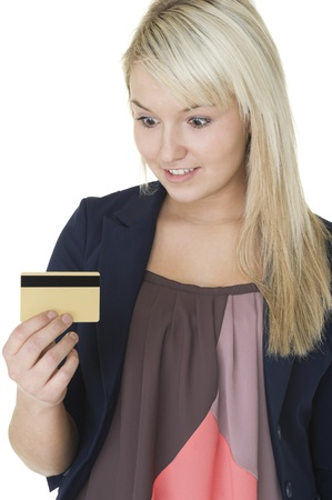 gleeful: Beautiful blonde woman with a gleeful smlie looking at her credit card with anticipation as she imagines all the purchases she can charge to it