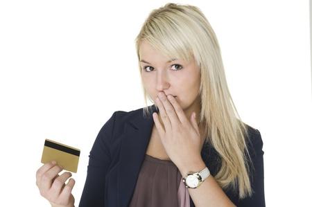 Mooie blonde vrouw met een schuldige blik en haar hand voor haar mond houdt ze haar creditcard waarop ze is gegaan op een uitgaven spree en uitgeven,