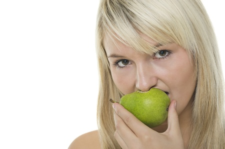 Attractive young blonde woman eating a half eaten healthy green pear, studio headshot isolated on white