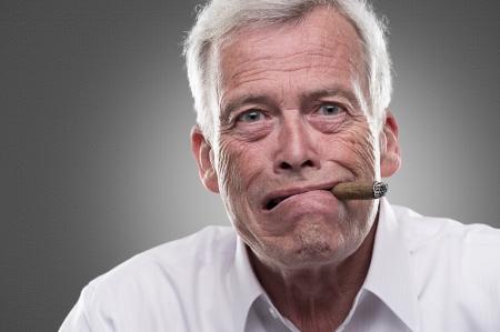 Studio shot van verbaasd senior man met sigaar in zijn mond