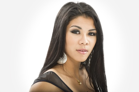 Studio headshot portrait of beautiful Asian woman with very long dark brunette hair posing sideways looking at the camera