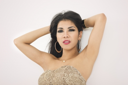 Low angle view of a sensual attractive Asian woman with a busty figure and her arms raised leaning against a wall Stock Photo