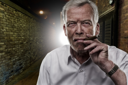 tenacious: Handsome determined senior man smoking a cigar outdoors in the darkness backlit by a light on a brick building Stock Photo
