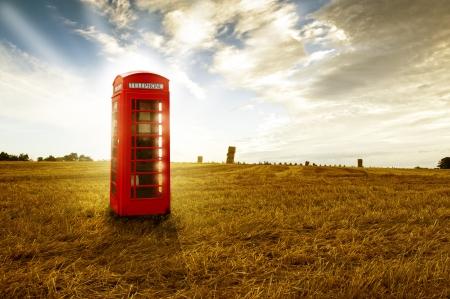 Ouderwetse traditionele rode telefooncel of openbare telefooncel staat in een open veld verlaten in avondlicht