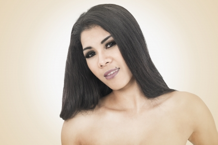 topless brunette: Head and shoulders studio portrait of a sexy beautiful Asian woman with bare shoulders and a sultry seductive look posing against a toned studio background with highlight surounding her head Stock Photo