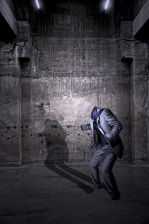 Spookachtige verschijning onzichtbaar - een geanimeerde stel kleren werpt een lange schaduw op een muur. Een spookachtige verschijning van een onzichtbaar persoon