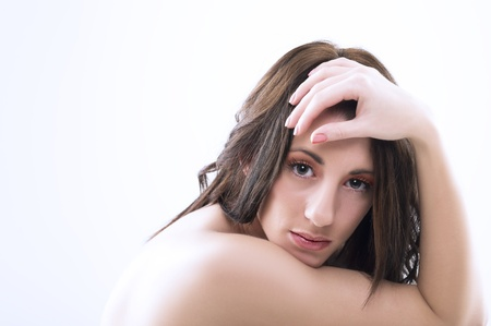 downhearted: Serious pensive attractive woman with bare shoulders and tousled long brunette hair looking directly at the camera in studio
