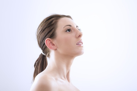 head on shoulder: Beautiful graceful woman witth bare shoulders craning her neck and looking upwards, head and shoulder portrait