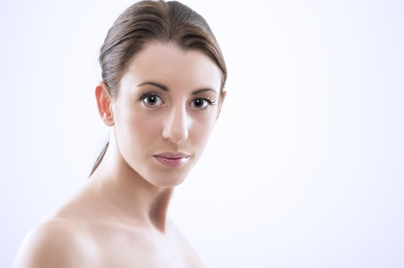 lustrous: Head and shoulders studio portrait of a beautiful sexy woman with bare shoulders, a natural complexion and her hair tied back in a ponytail looking at the camera with large lustrous eyes Stock Photo
