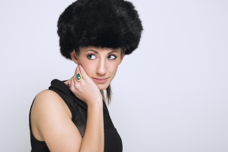 Head and shoulders portrait of a beautiful slender sophisticated woman modeling a winter fur hat against a white studio background with copy space photo