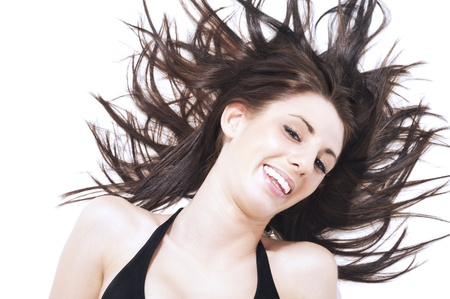 tresses: Laughing carefree young woman tossing her long brunette hair which is spreading out in the wind around her head in a fan shape