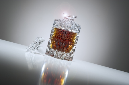 dispense: Tilted low angle view of an open elegant crystal whiskey or brandy decanter with a sparkling rim and a graduated grey background with a highlight and reflection Stock Photo