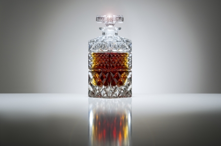 Luxury stoppered cut crystal decanter filled with whiskey or brandy on a graduated grey background with highlight and reflection