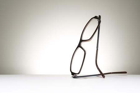 Paar moderne modieuze bril in evenwicht in een rechtopstaande positie op een witte studio achtergrond met copyspace conceptuele visie, correctie, optometrie en gezondheidszorg Stockfoto
