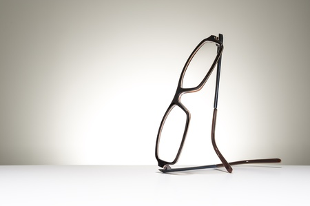 myopic: Pair of modern fashionable spectacles balanced in an upright position on a white studio background with copyspace conceptual of vision, correction, optometry and healthcare