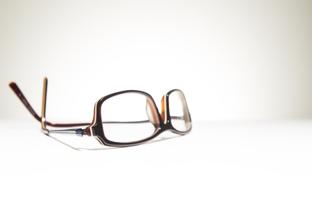 A pair of classic framed reading glasses resting on a white background with space for text Stock Photo
