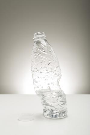 reciclable: Twisted distorsionada botella transparente de plástico de agua cubierto de gotas de agua perlas de pie en posición vertical sobre una encimera de estudio sobre un fondo neutro gris con resalte Foto de archivo
