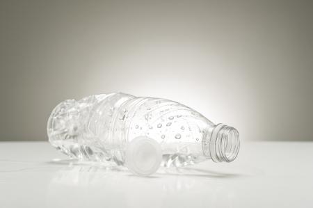 reciclable: Claro botella de plástico vacía con gotas de agua situadas en su lado en una encimera blanca junto a la tapa después del consumo de una bebida refrescante pura