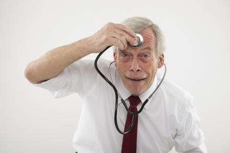 Humoristische medische concept van een senior man trekt een komisch gezicht met een stethosope op zijn voorhoofd, alsof het controleren van zijn hersenfuncties, intellect, wijsheid of cognitieve bevoegdheden