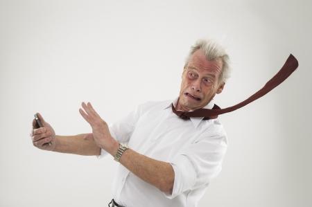 Knappe hogere zakenman mishandeling door de sterke wind met zijn stropdas zweepslagen uit Stockfoto