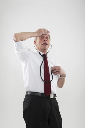 Leuk portret van een hypochonder man bezorgd over zijn gezondheid met een hand op zijn voorhoofd tijdens het luisteren naar zijn hart met een stethoscoop met de andere, of als een waarschuwing van hart-en vaatziekten bij ouderen Stockfoto
