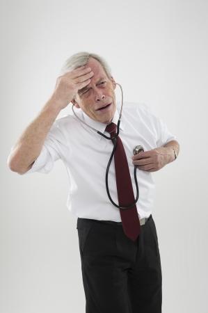 Oude man, die zich onwel voelen, probeert zijn diagnose te stellen zijn eigen ziekte met de hulp van een stethoscoop Stockfoto