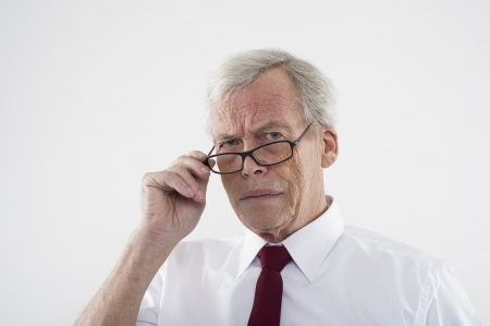 Handsome retired man in glasses peering over the top of the frames at the camera with a frown, head and shoulders studio portrait Stock Photo